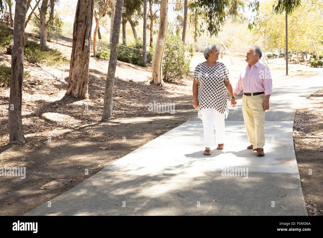 Senior couple walking hand in hand, outdoors - Stock Image