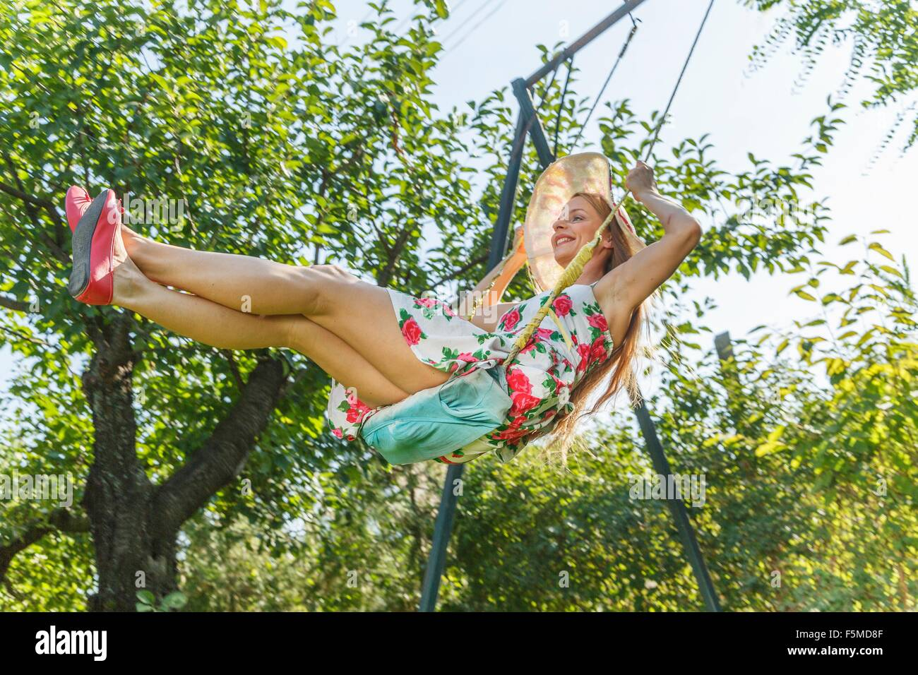 Mid adult woman swinging on garden swing, low angle view Stock Photo