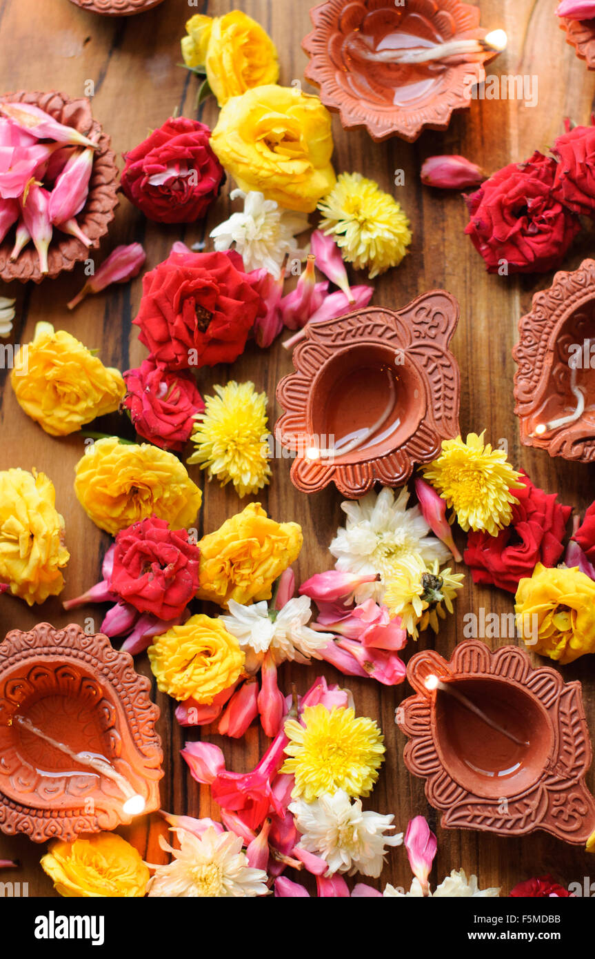 Diwali Diyas on a wooden background with festive flowers and lights - Stock Image