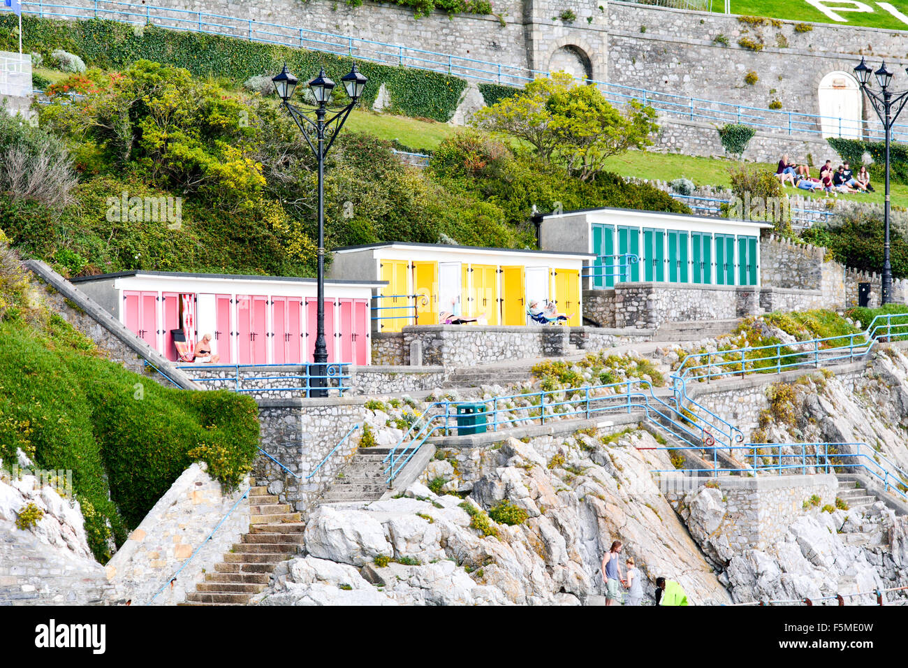 Beach Huts With Red Green Or Yellow Doors On Rocks Overlooking Sea