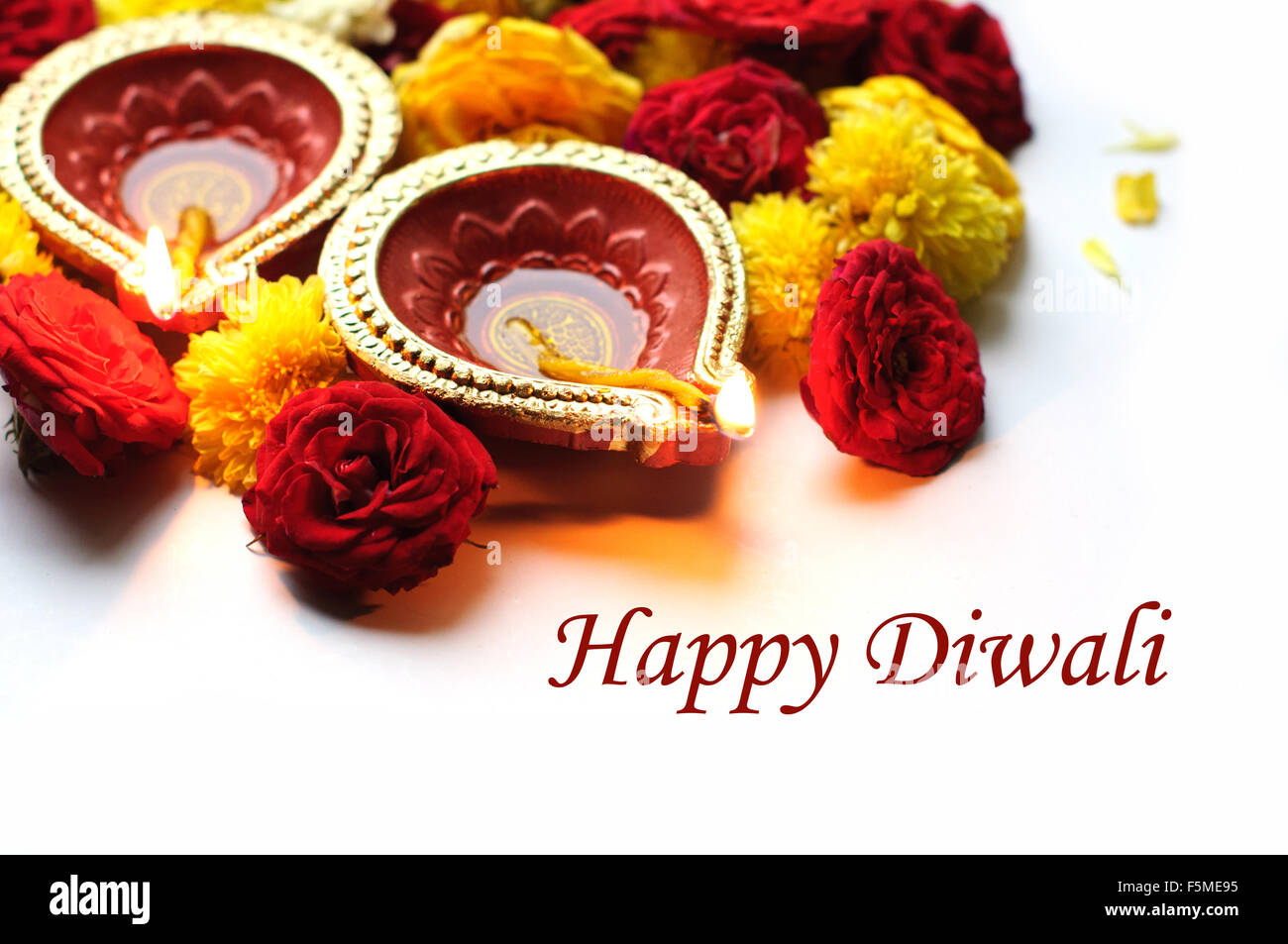 Diwali Diyas on a wooden background with festive flowers and lights Stock Photo