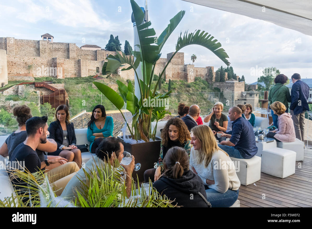 People at rooftop terrace bar and Alcazaba Moorish castle in background. Malaga, Andalusia, Spain - Stock Image