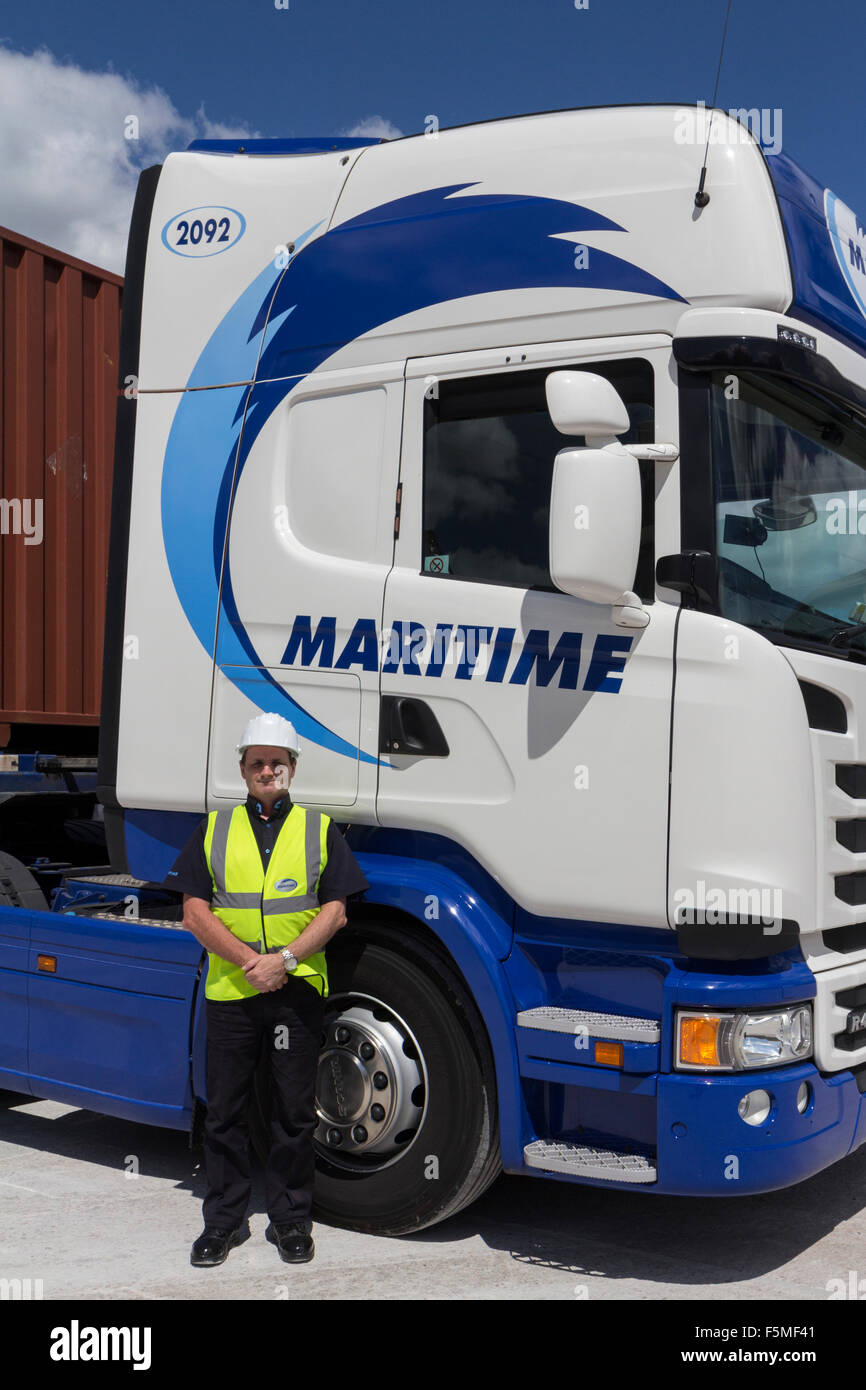 A lorry driver in safety clothing standing beside his vehicle - Stock Image