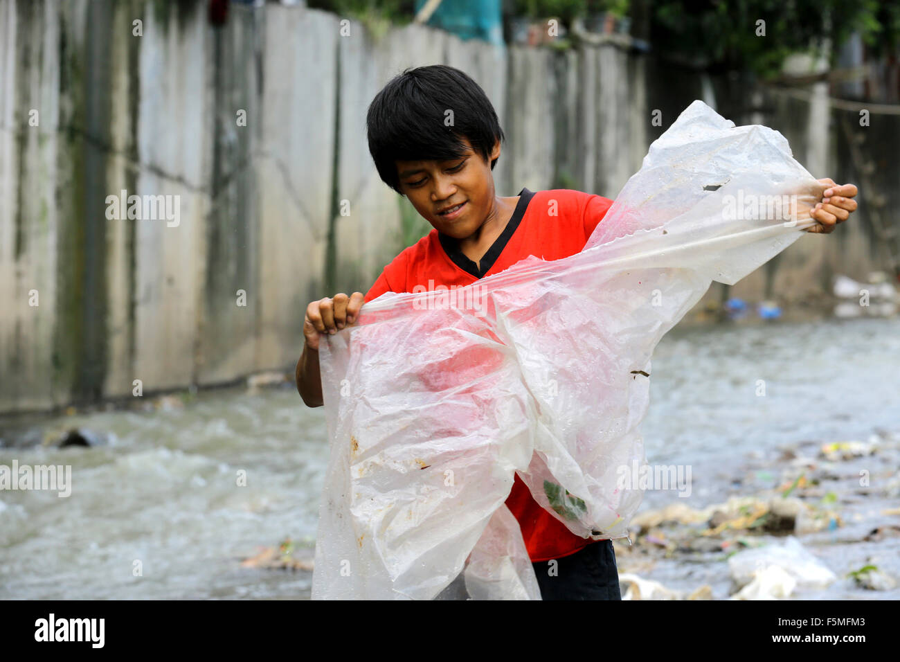 A boy  washes plastic sheets in a stream to supply them to recycling. Near to a garbage dump in Montalban, Quezon - Stock Image