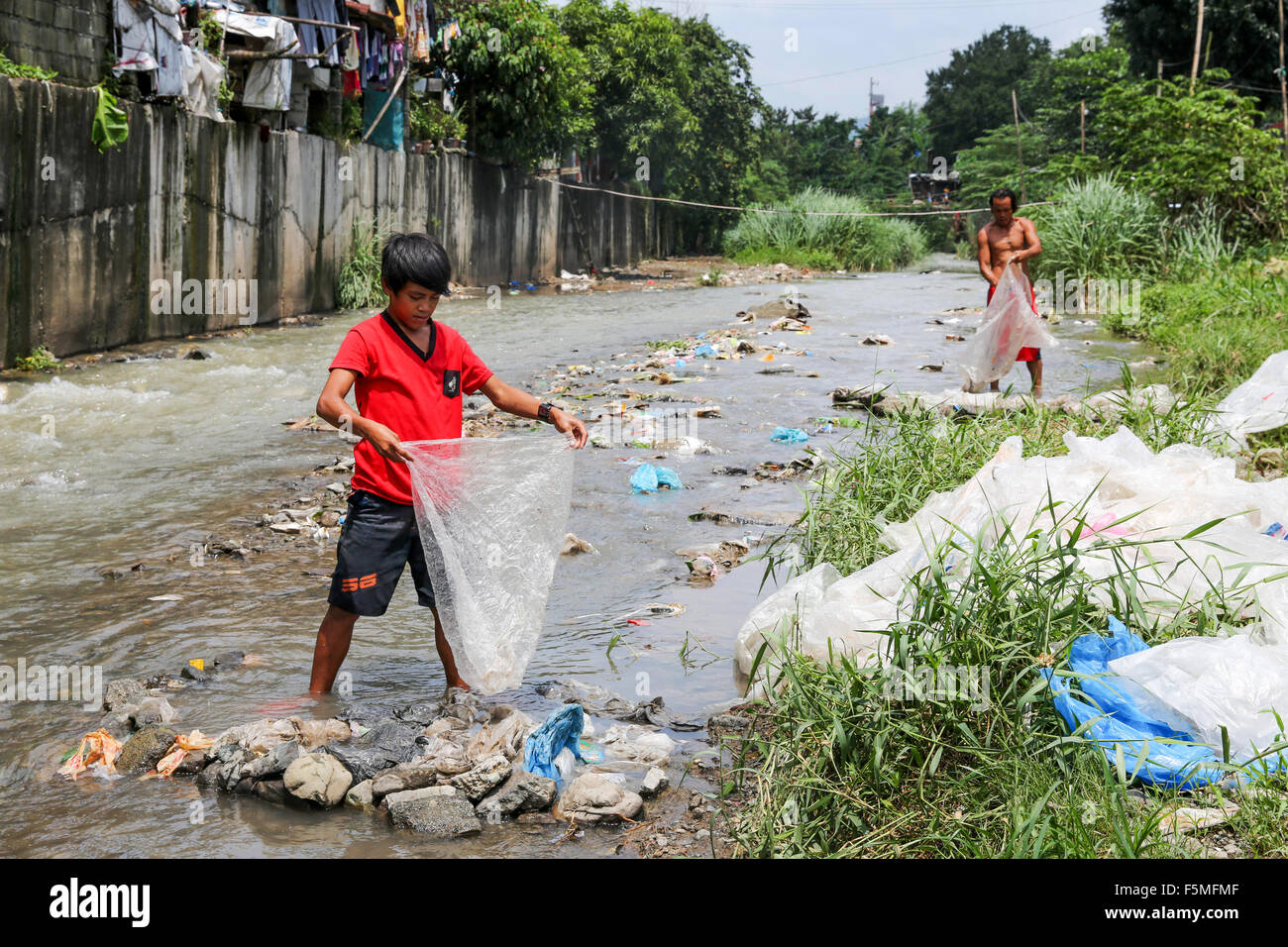 A boy  washes plastic sheets in a stream to supply them to recycling. Near to a garbage dump in Montablan, Quezon - Stock Image