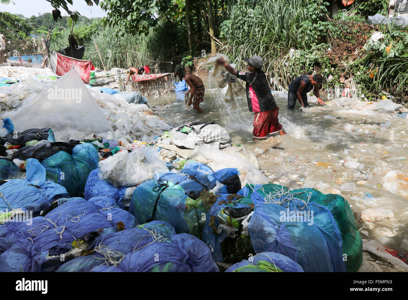 Garbage collectors washing plastic sheets in a stream to supply them to recycling. Near a garbage dump in Montablan, - Stock Image