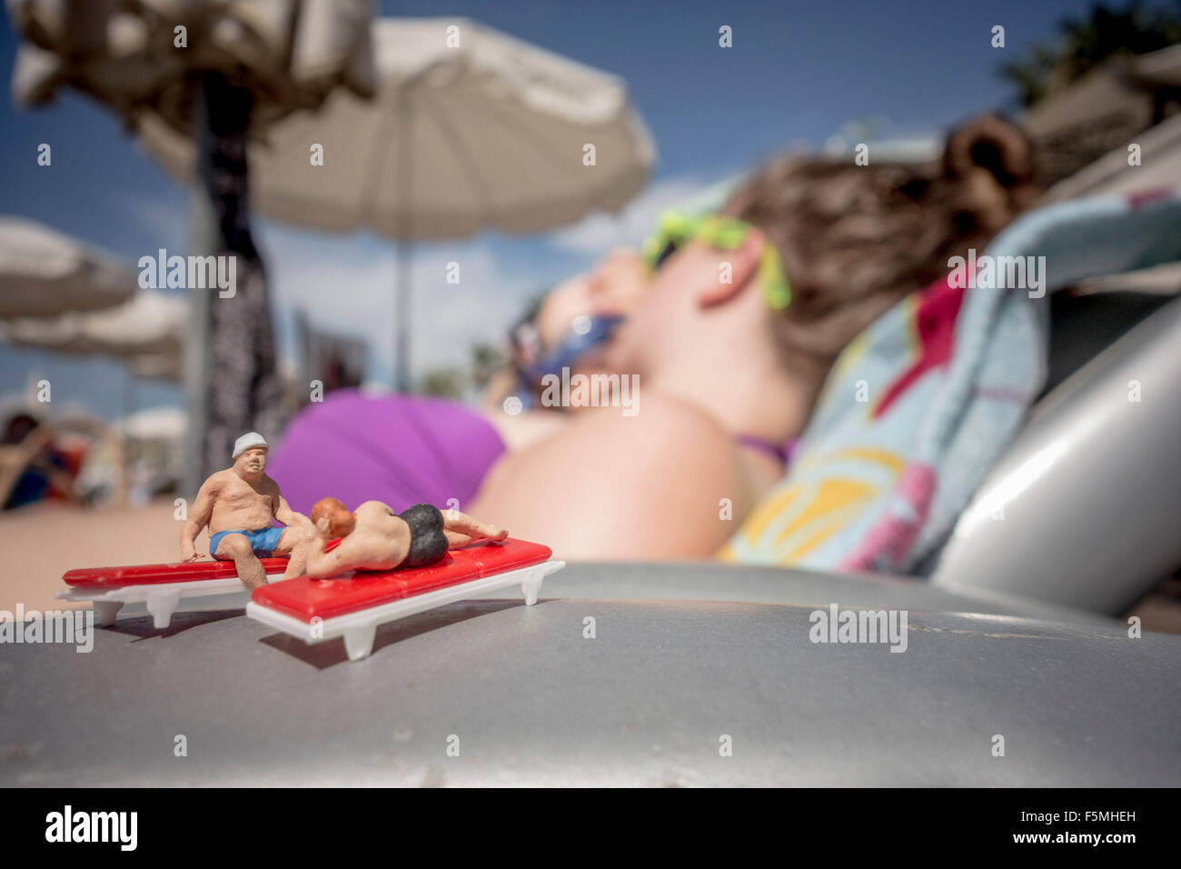 Two figurines on sun loungers at the beach - Stock Image