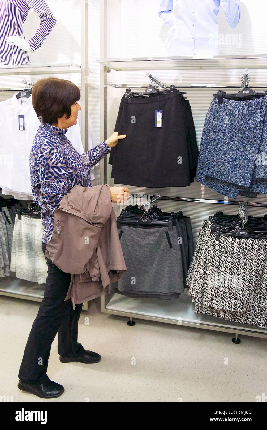 Middle aged woman shopping for skirt in a superstore. Rails of skirts on the wall. Stock Photo