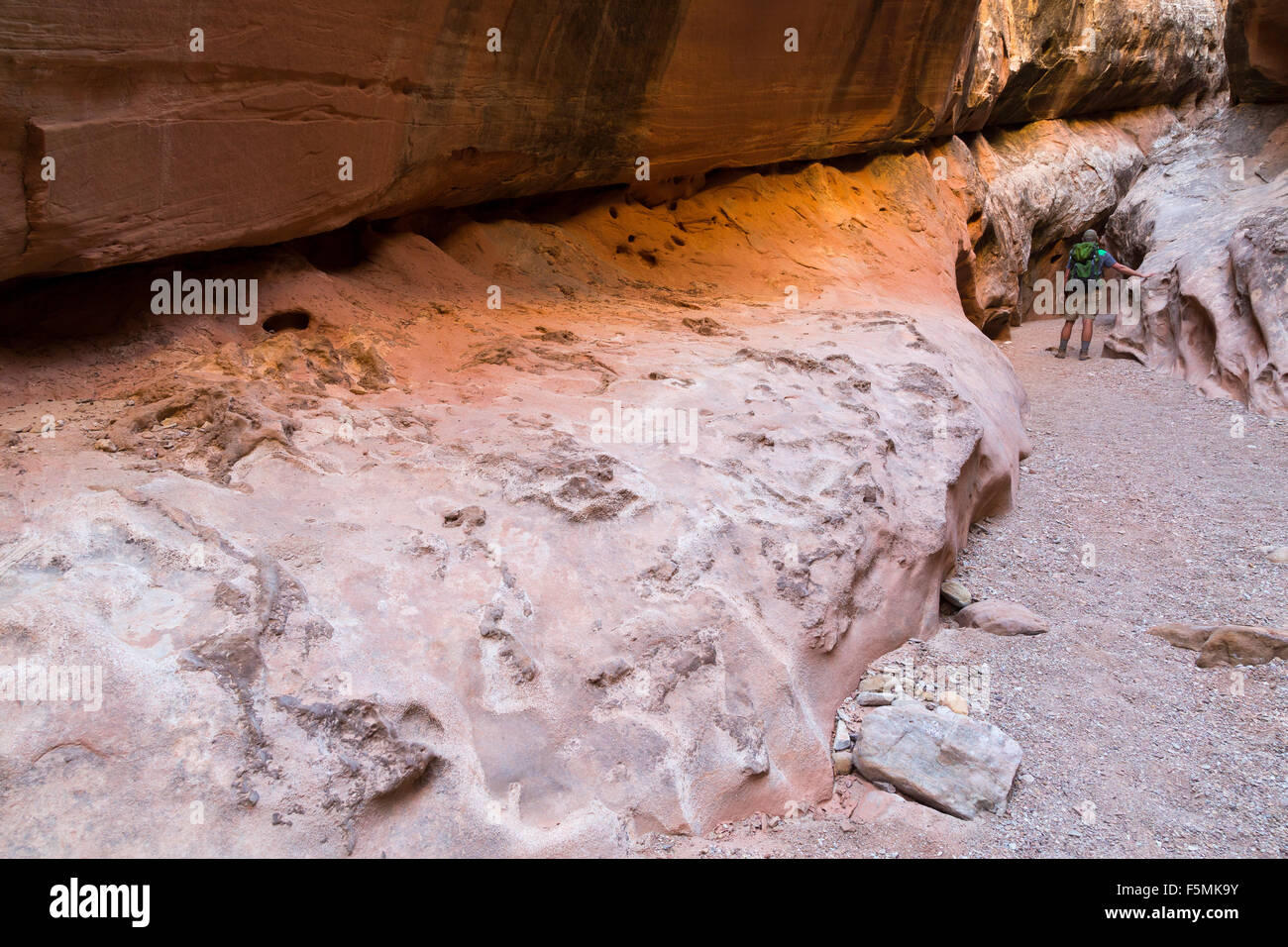 A hiker passing through a large opening in a slot canyon in Little Wild Horse Canyon, San Rafael Swell, Utah Stock Photo