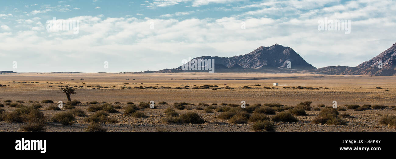 A lonely car is driving through the wide hot Namib desert in Namibia. - Stock Image