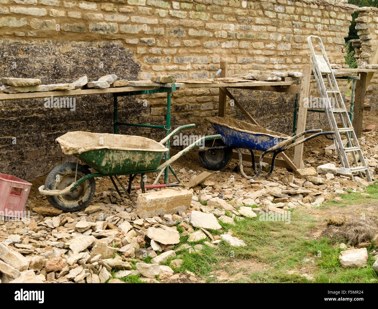 Old natural, limestone garden wall renovation and repair with builder's tools, wheelbarrows, trestles, scaffolding - Stock Image