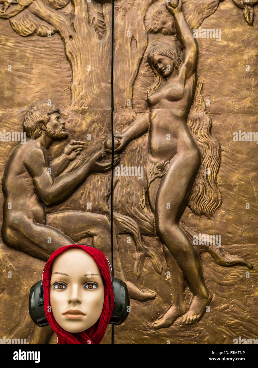 Genara listening to music, indifferent to the environment, to a high relief depicting Eve offering Adam the apple. - Stock Image