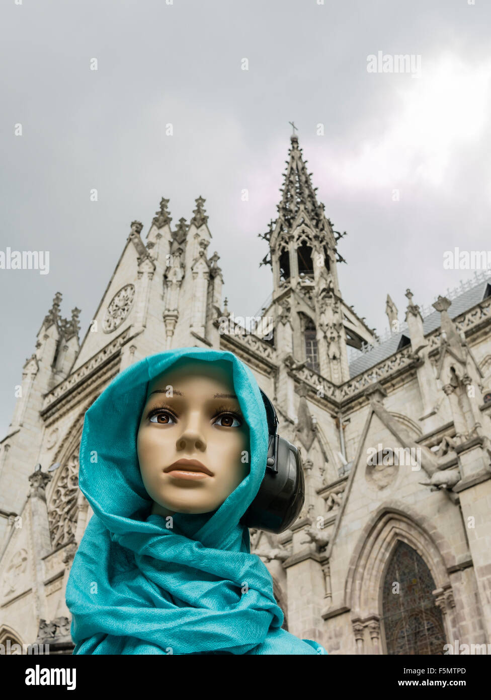 Genara listening to music, indifferent, to the splendid tower of the Basilica of the National Vow. Quito, Ecuador. - Stock Image