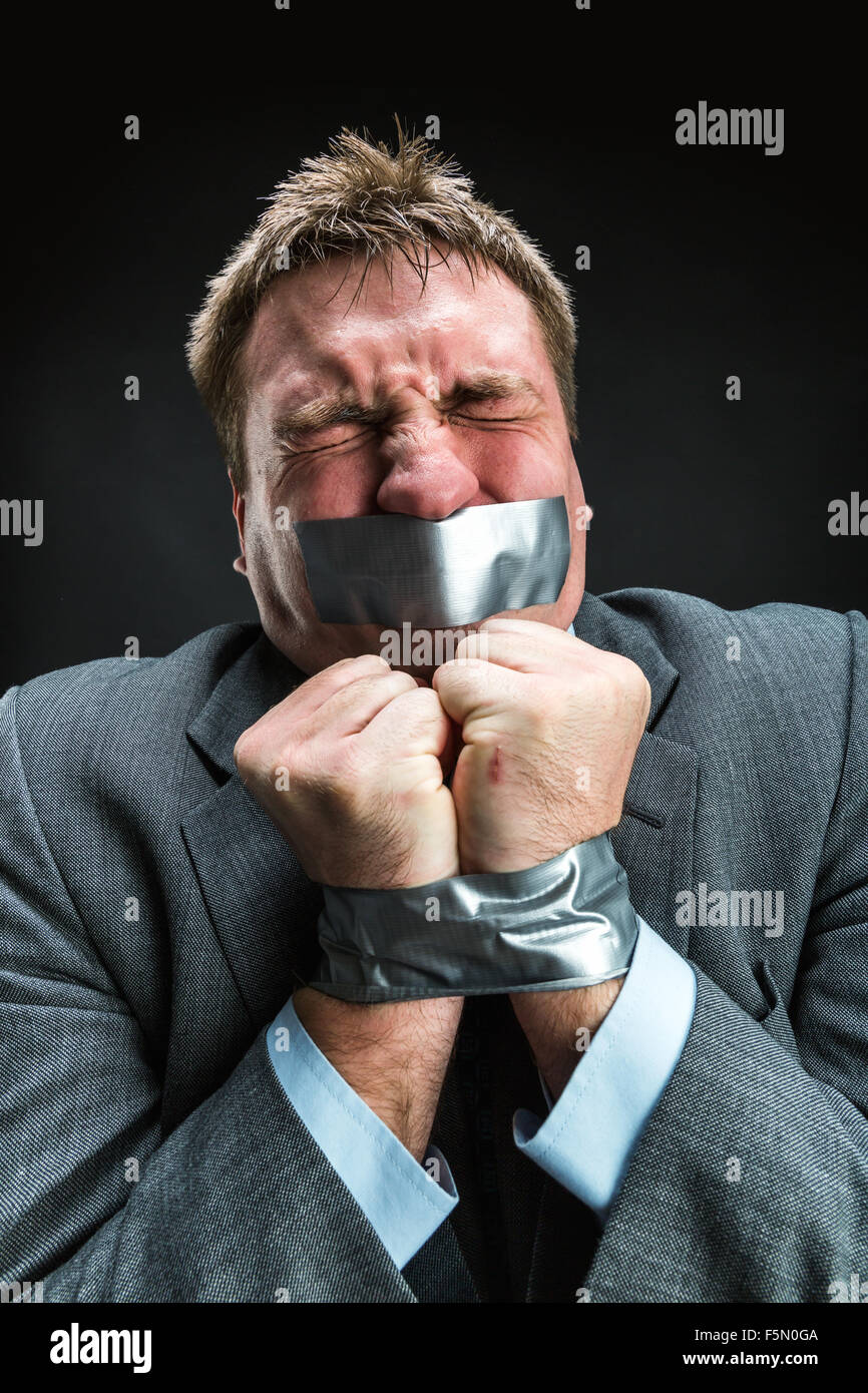 Man with mouth and hands  covered by masking tape preventing speech, studio shoot - Stock Image