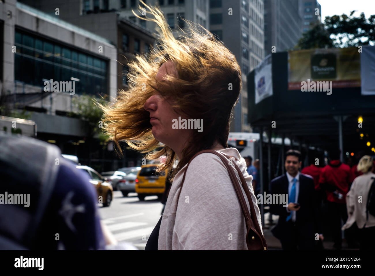 New York City, New York, USA.  November 11, 2015:  A strong wind blows a woman's hair over her face. - Stock Image