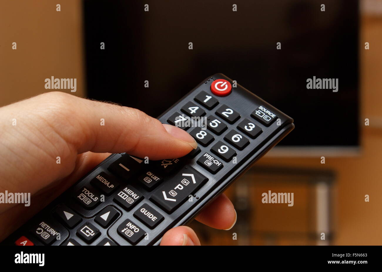 Hand Holding Infrared Remote Control For Television And Tv Screen In Background Choosing Program To Watch