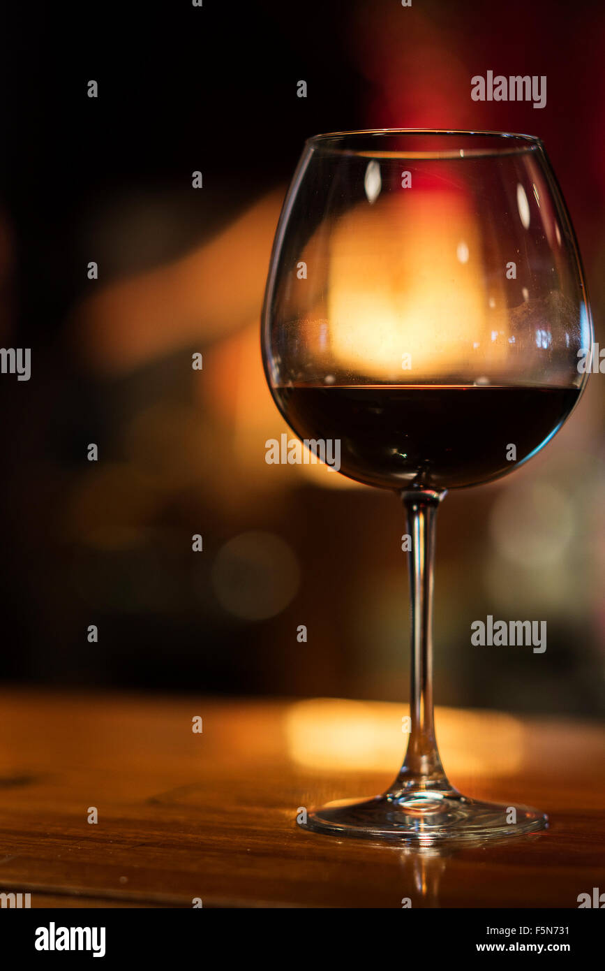 glass of red wine in cozy bar interior at night - Stock Image