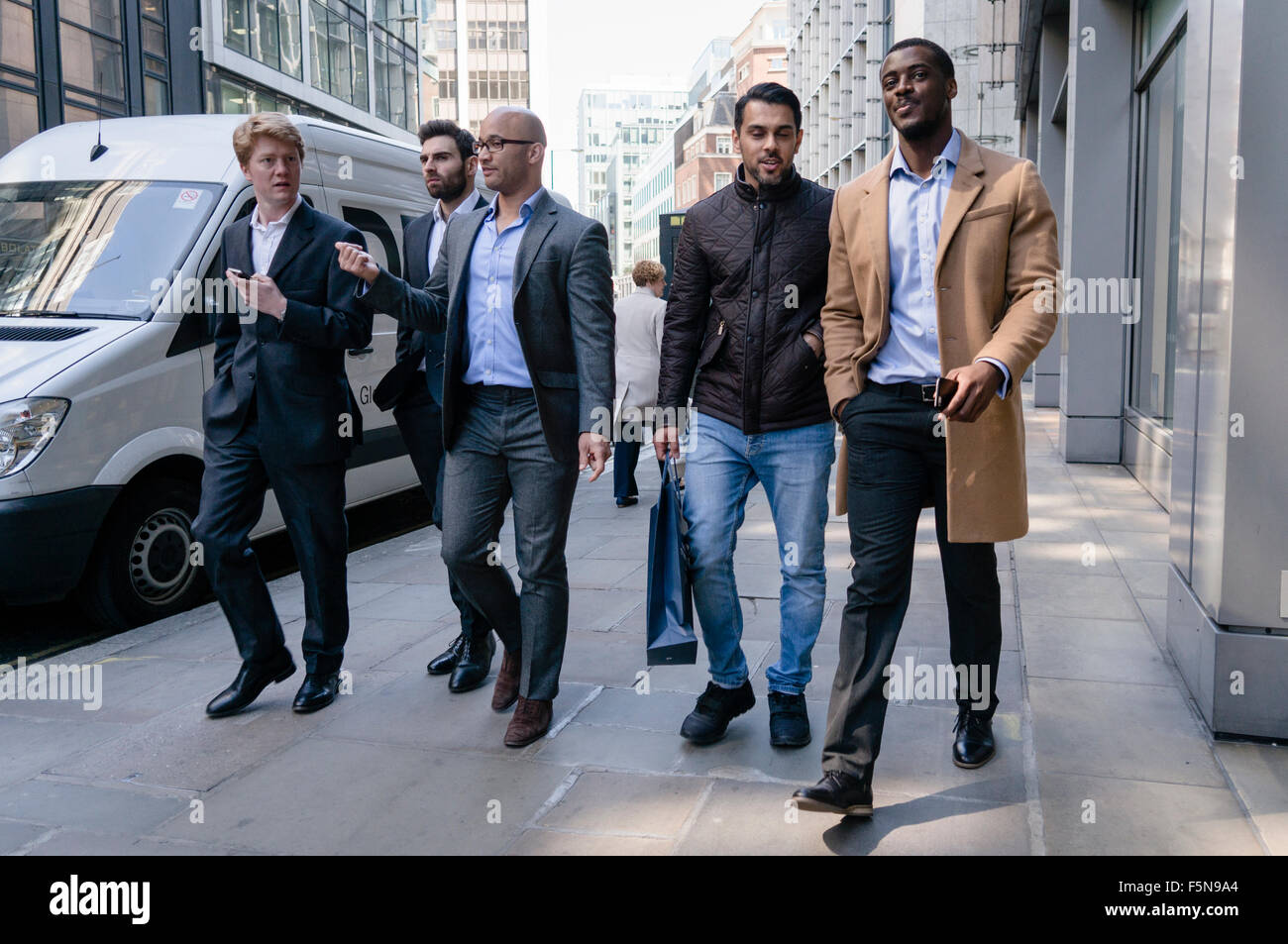 Young men walk down a street in the City of London Stock Photo