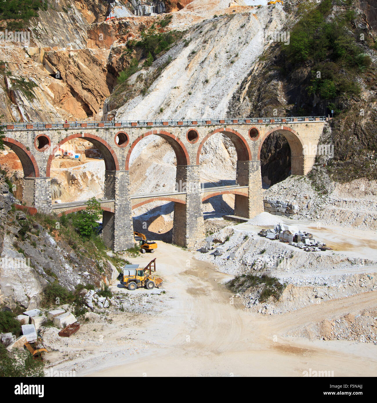 White marble quarry old bridge and excavators at work. Apuan Alps, Carrara, Tuscany, Italy, Europe - Stock Image