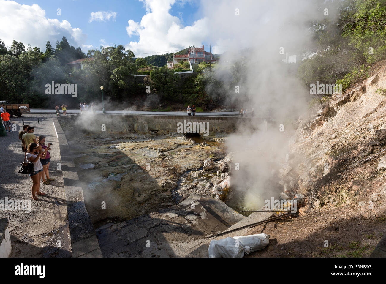 People taking pictures to geysers, hot-springs and fumaroles scattered in the central village of Furnas, São - Stock Image