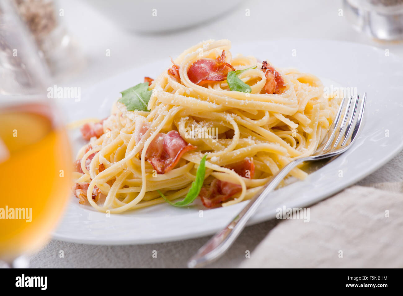 Plate of carbonara pasta with bacon and grated cheese - Stock Image