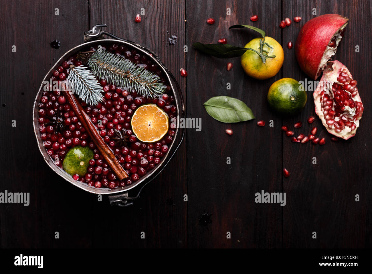 Cranberry mandarin pomegranate punch or mulled wine in a rustic aged pot - Stock Image