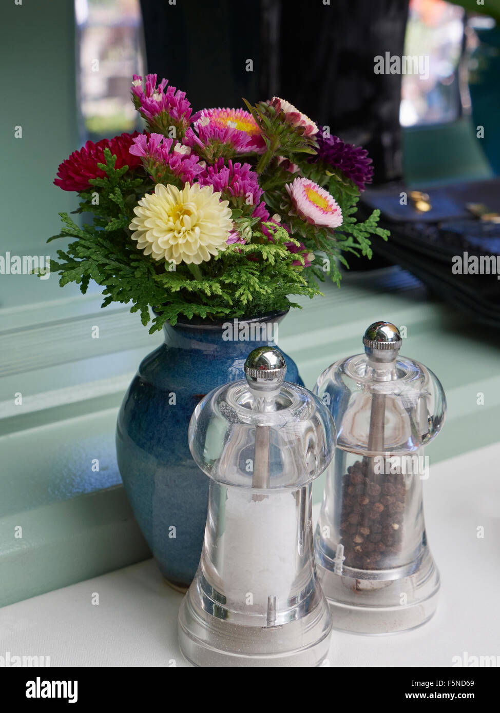 Small vase of fresh flowers with salt and pepper mills on a dining table - Stock Image