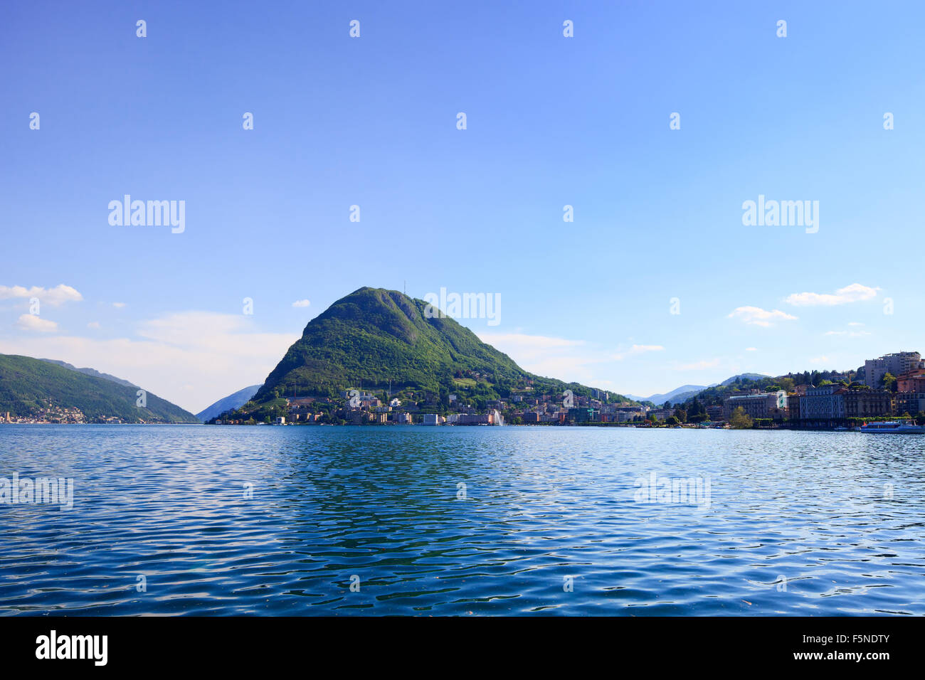 Lugano lake and mountains landscape. City, water, blue sky and mountains. Ticino, Swiss or Switzerland, Europe. Stock Photo