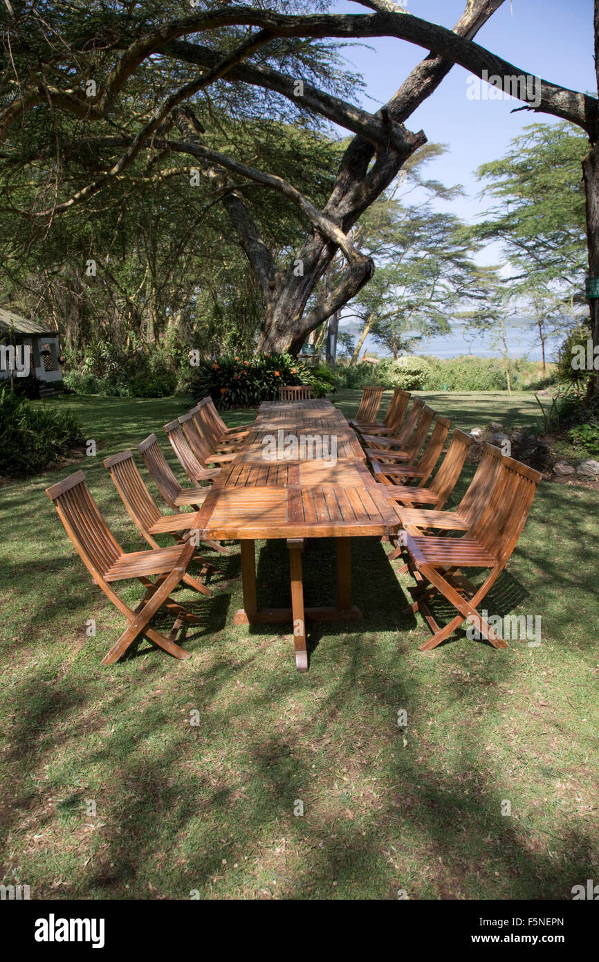 Unoccupied table and chairs on lawns at Elsamere Lake Naivasha Kenya - Stock Image
