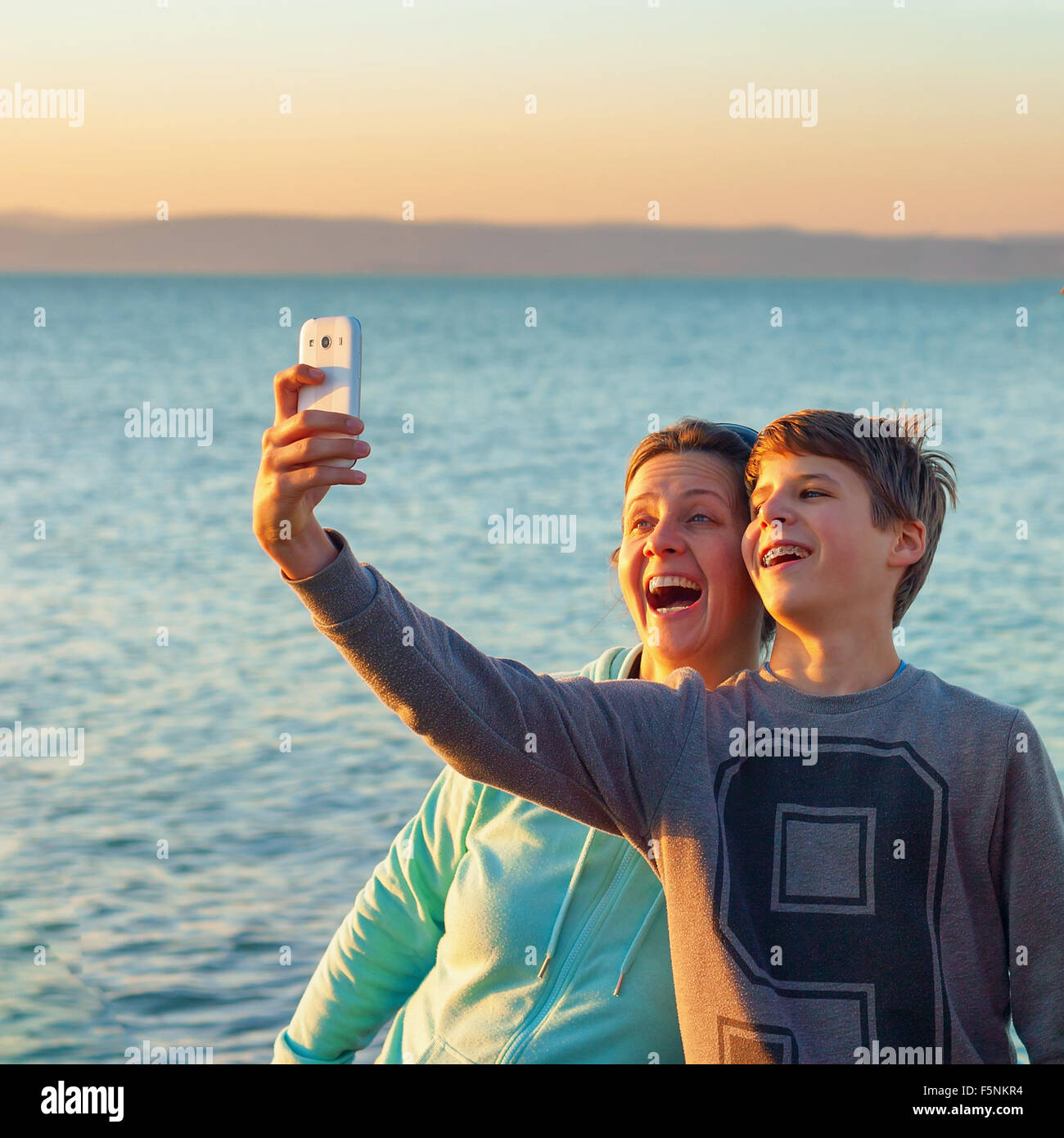 Young boy and a happy adult woman taking a selfie in front of a lake the boy has braces on his teeth - Stock Image