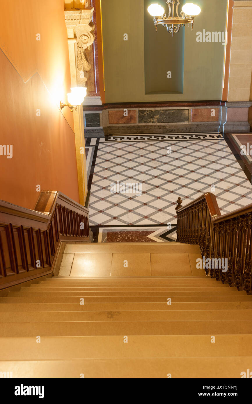 Stairs leading down to tiles diamond pattern floor in French Renaissance style, interior . - Stock Image