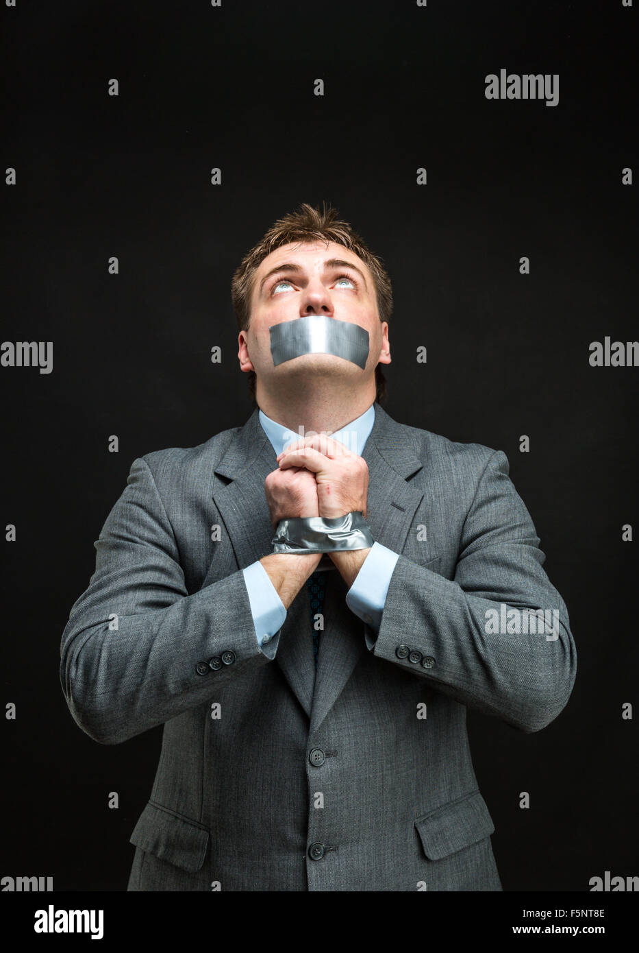 Man with mouth and hands covered by masking tape preventing speech, isolated on black - Stock Image
