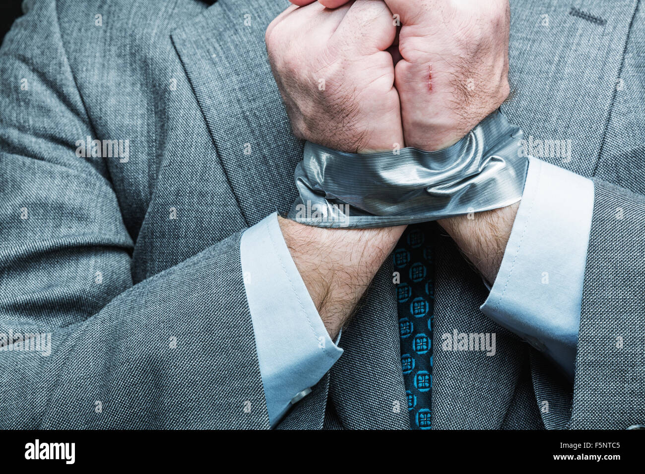 Businessman with hands covered by masking tape, studio shoot - Stock Image