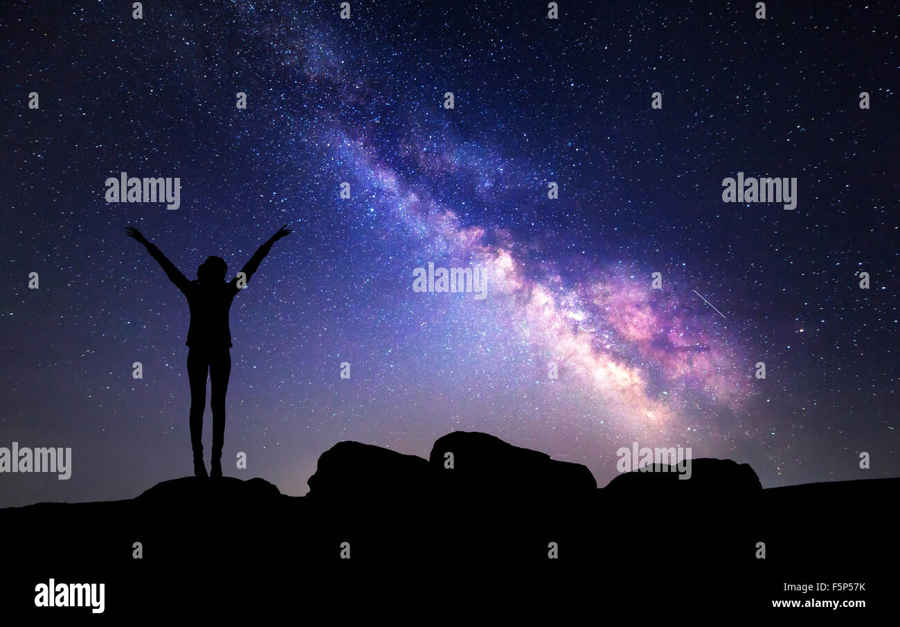 Milky Way. Night sky with stars and silhouette of a woman practicing yoga. - Stock Image