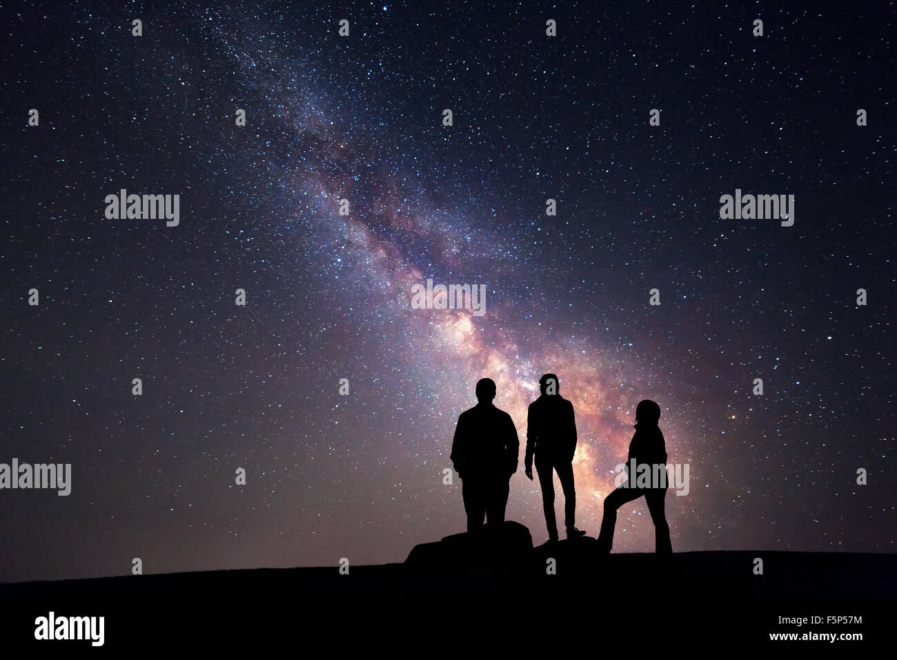Milky Way. Night sky with stars and silhouette of a happy family with raised-up arms - Stock Image