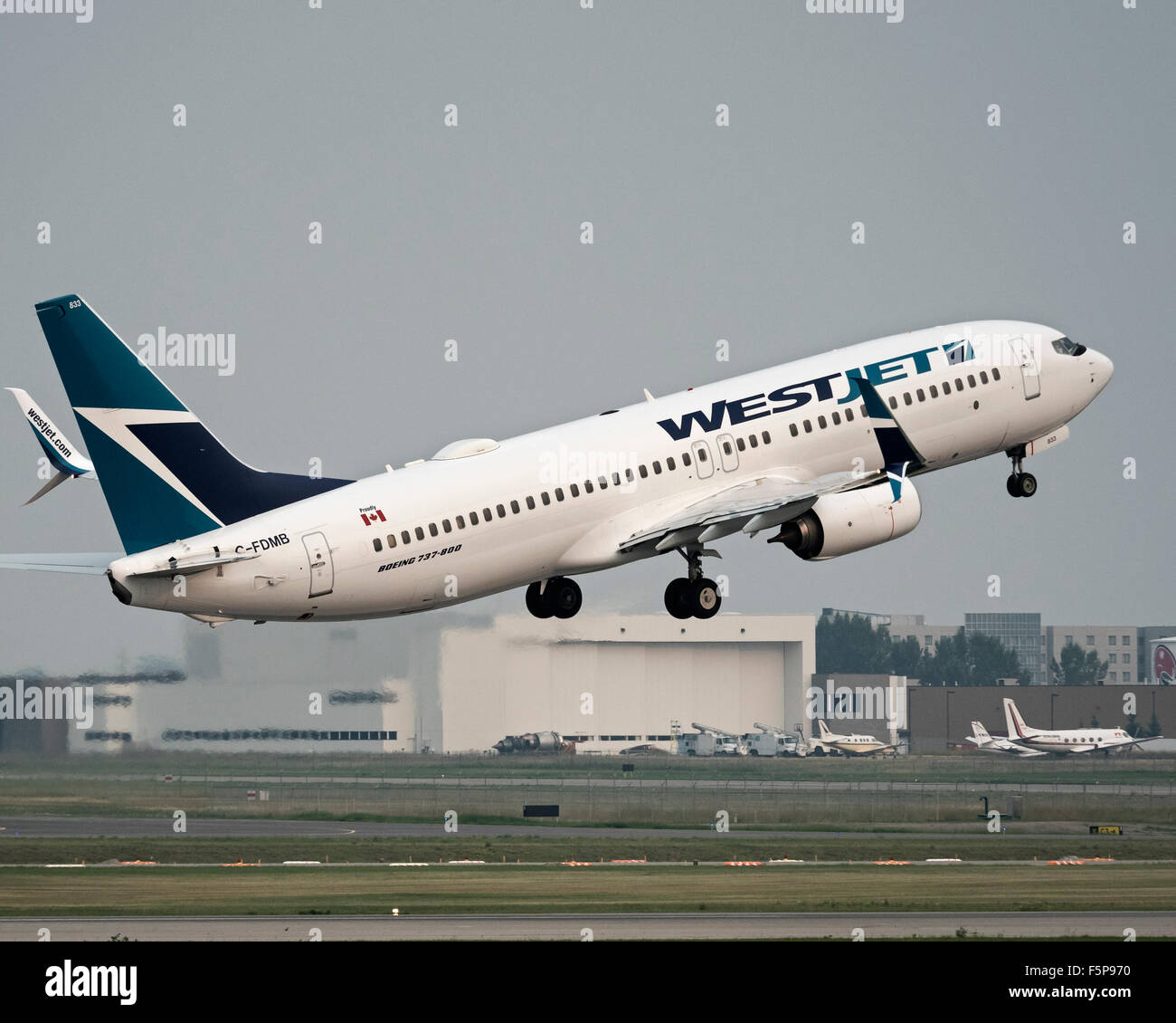 A Westjet Boeing 737-800 (C-FDMB) jetliner takes off from Calgary International Airport - Stock Image