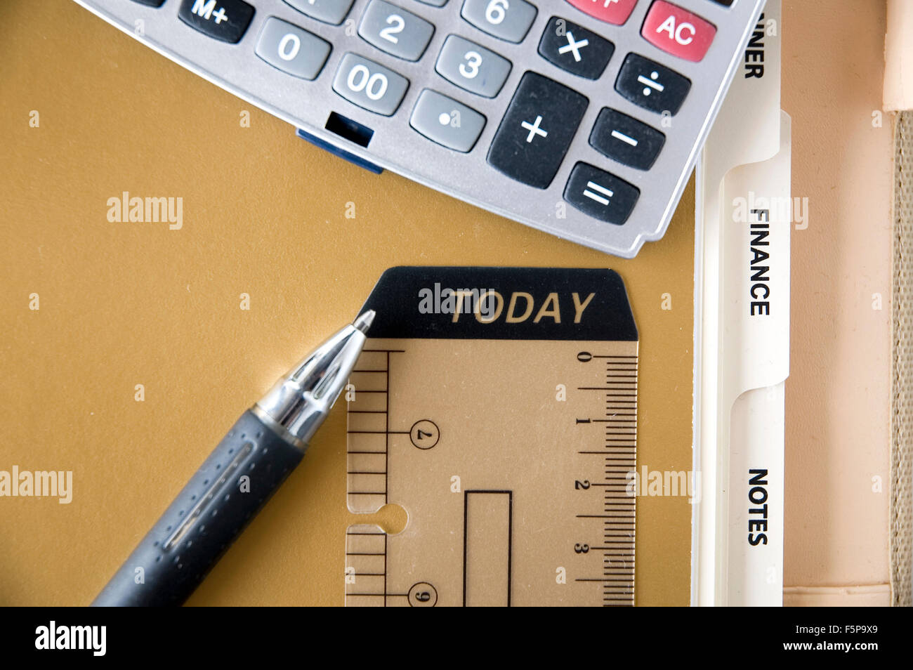pen point to today tag with calculator put on finance page Stock Photo
