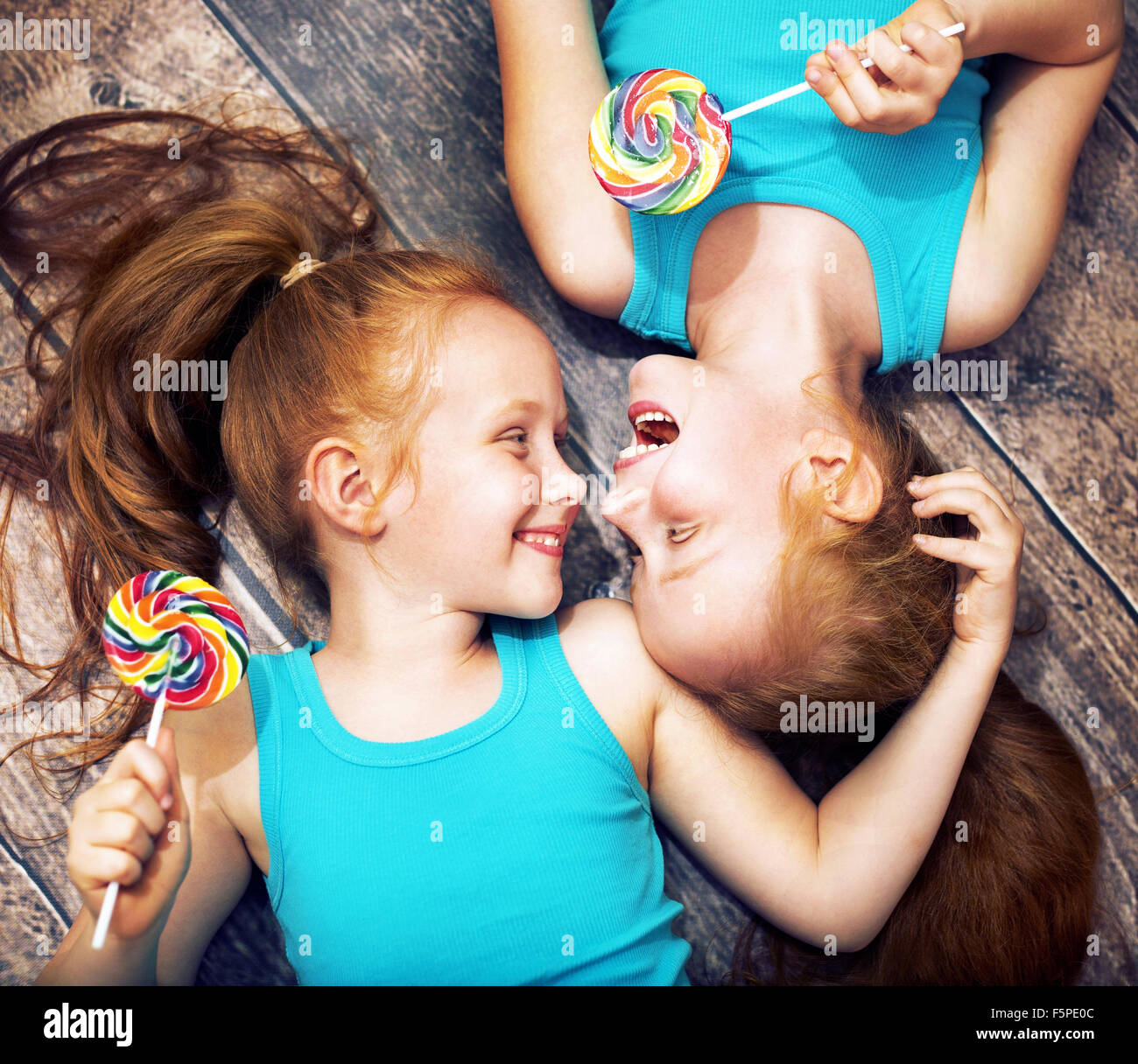 Fine portrait of a twin sisters holding colorful  lollipops - Stock Image