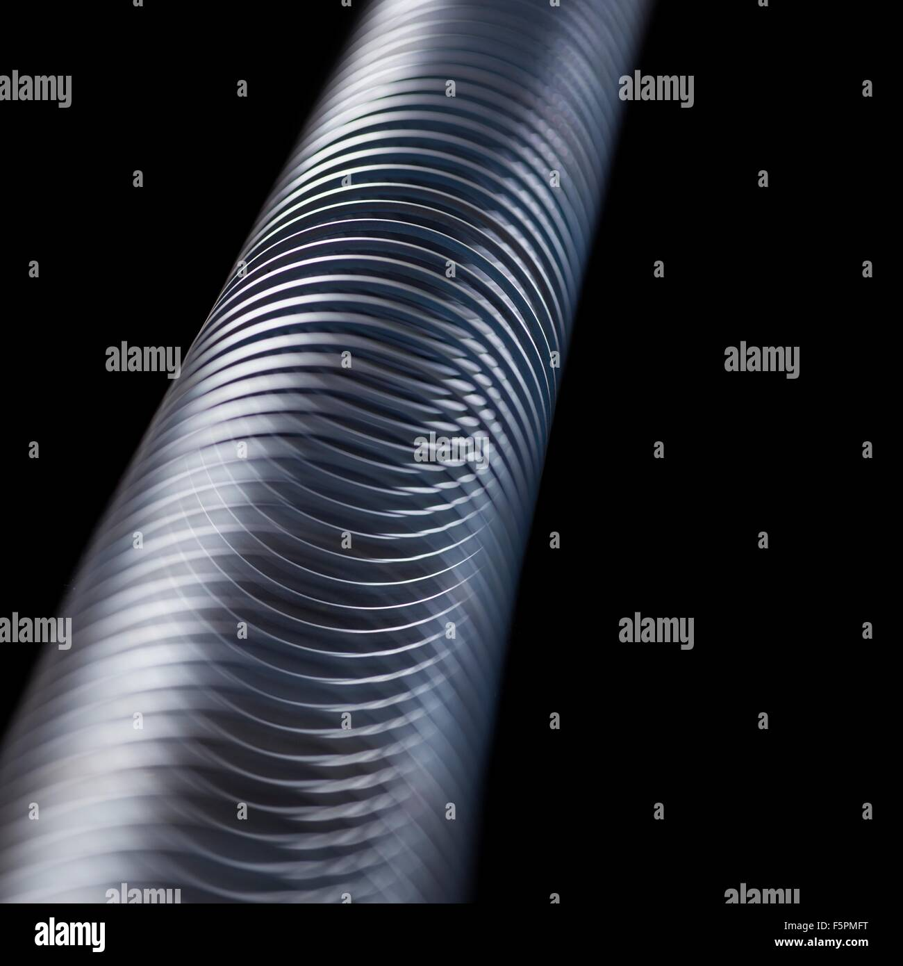Longitudinal wave in a slinky spring. In longitudinal (or compression) waves the displacement is along the axis Stock Photo