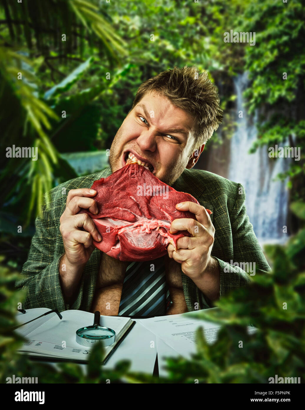 Hungry man is eating red fresh meat - Stock Image