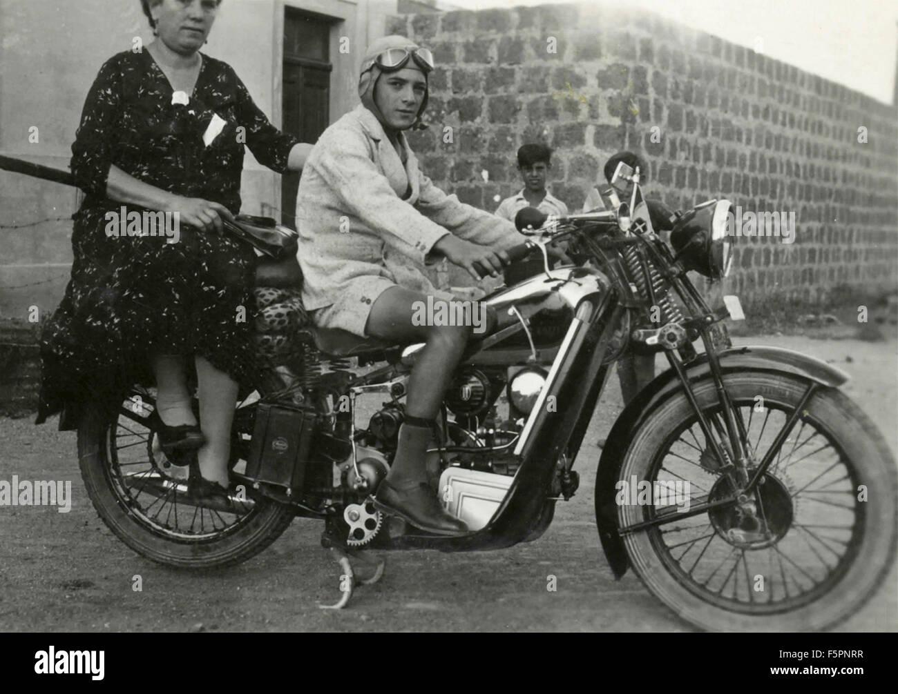 Boy with a woman on Moto Guzzi motorbike, Italy - Stock Image