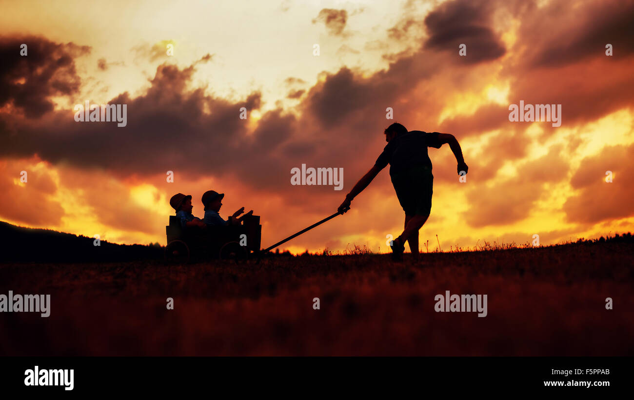 Glad father drawing a wooden carriage with his boys - Stock Image