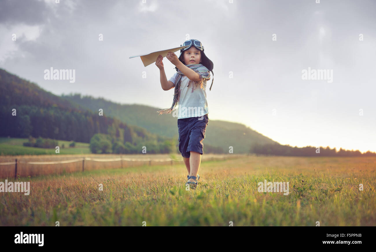 Cute little boy playing paper plane - Stock Image