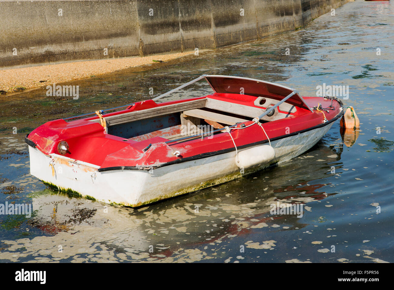 Sad looking speedboat, clearly in need of some TLC. Red and white boat only just afloat in murky water - Stock Image