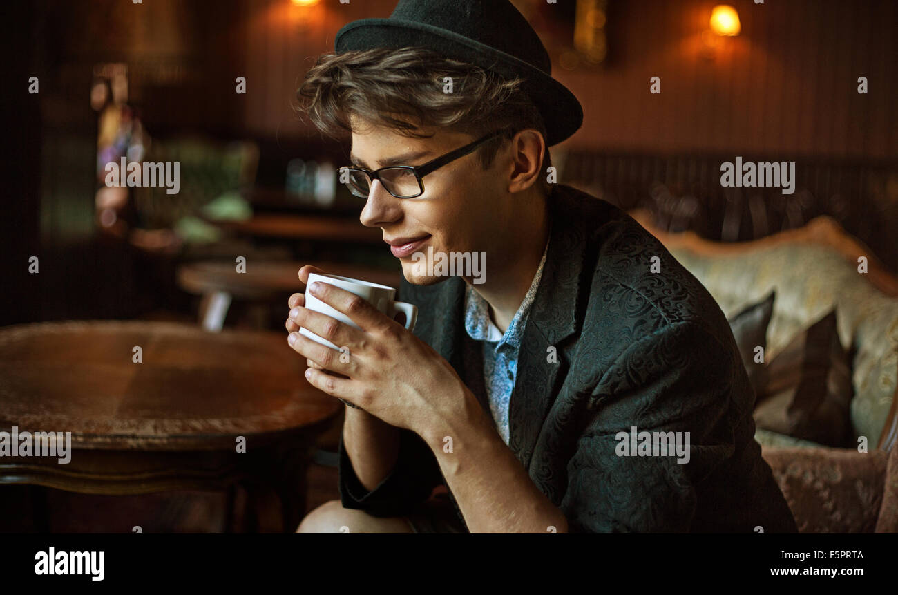 Glad elegant guy drinking a coffee - Stock Image