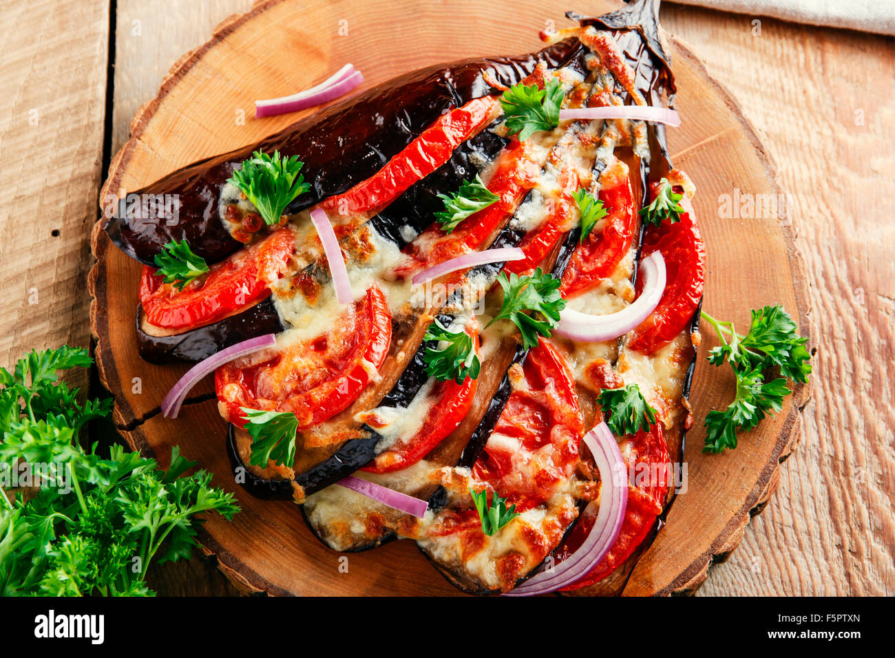 baked eggplant with cheese and tomatoes on a wooden surface Stock Photo