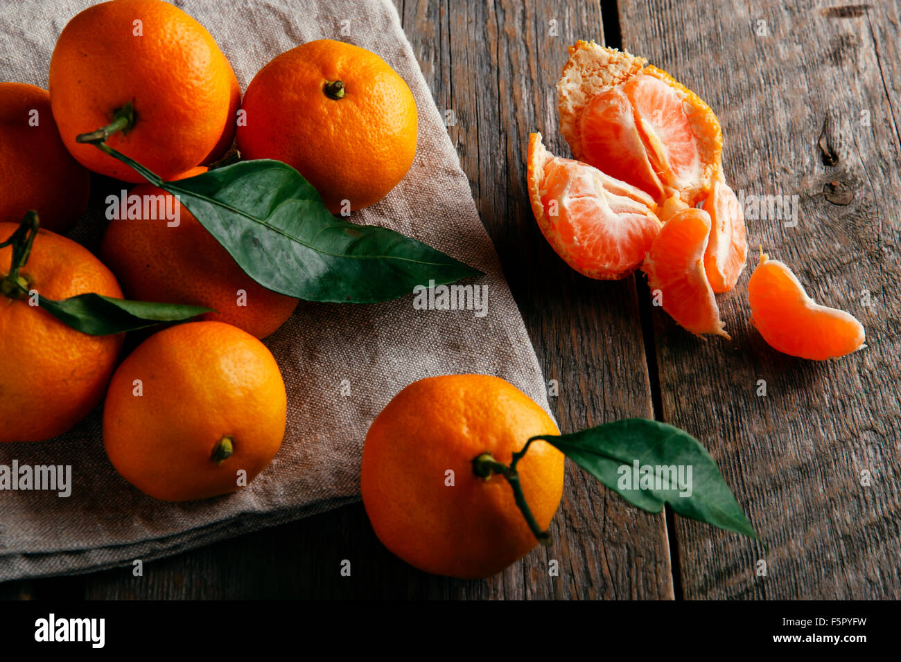 Ripe tangerines with leafs on wooden table - Stock Image