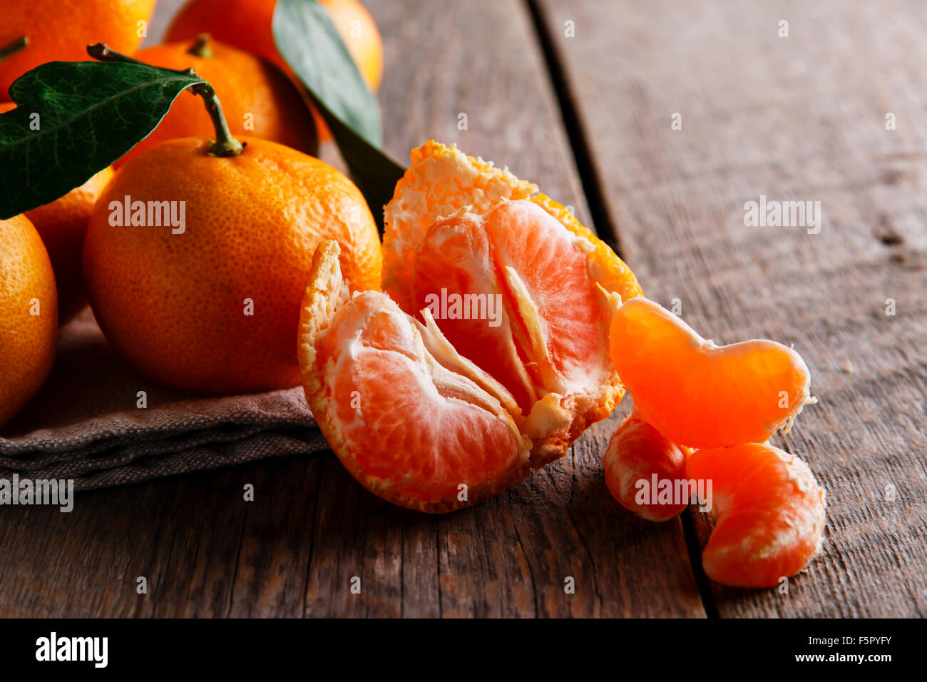 Ripe tangerines with leafs on wooden table Stock Photo