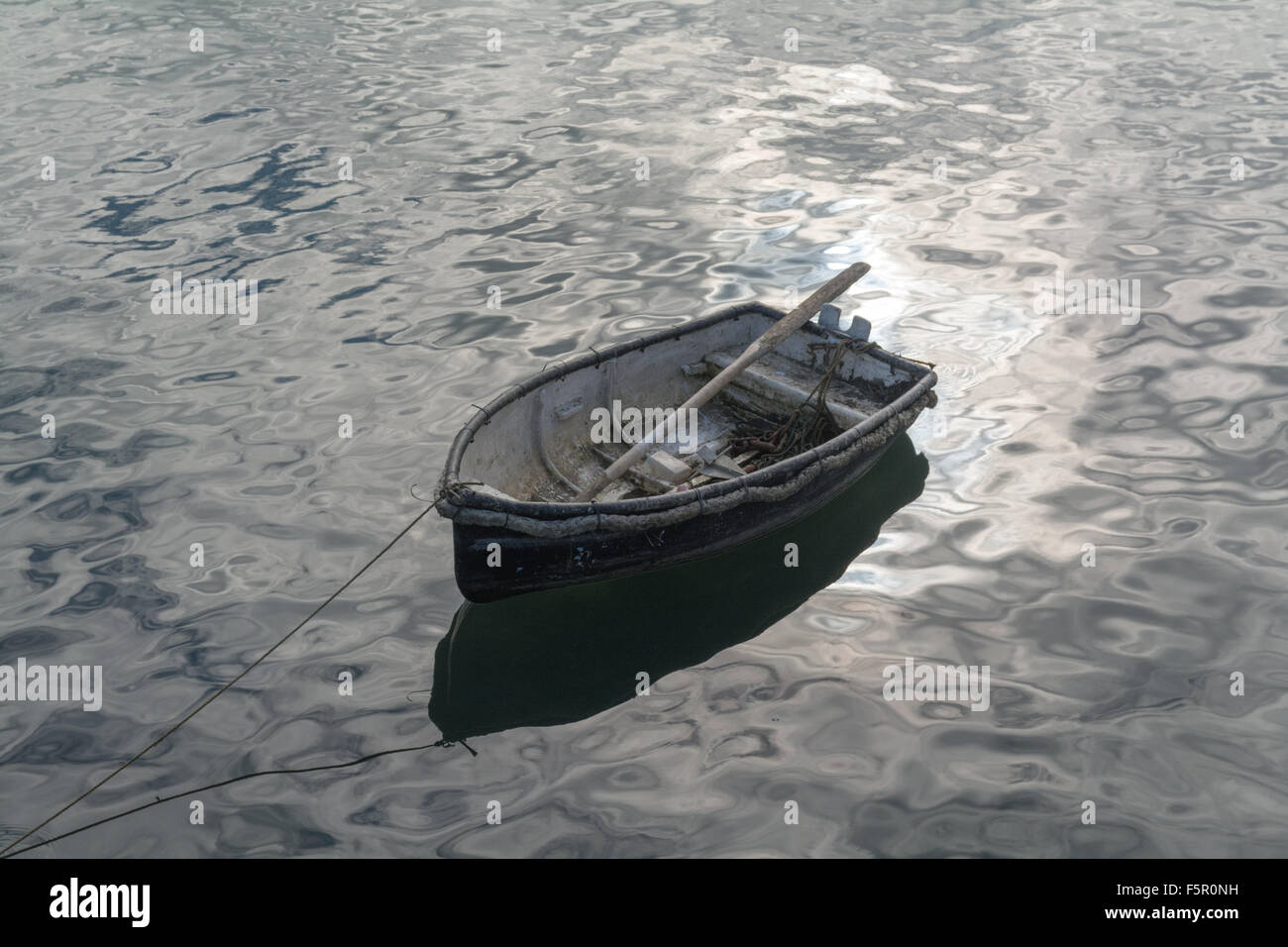 Small, old rowing boat in a harbour with bright light reflecting from surface - Stock Image