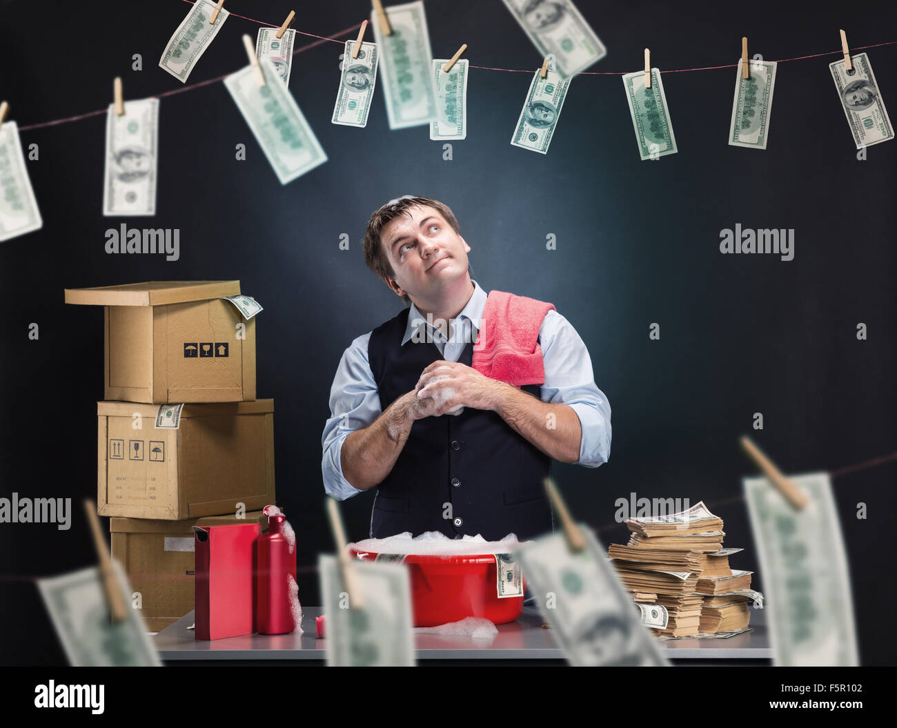 Glad businessman is laundering money banknotes in foam in red washbowl - Stock Image